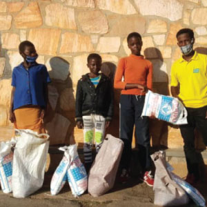 Jean de Dieu, our RDO from Nyamagabe district, distributes large sacks of flour and beans to families in his community