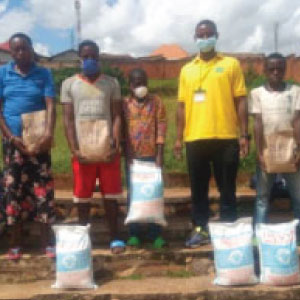 Laurien, RDO from Muhanga district distributes sacks of flour and beans to vulnerable families