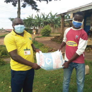 Our RDO from Ruhango district, Joseph, hands over a large sack of flour